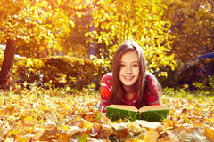 Muchacha que miente en las hojas caidas y que lee un libro Fotografía de archivo libre de regalías