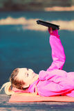Muchacha que miente en parque usando la tableta Imágenes de archivo libres de regalías