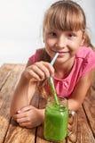 Muchacha que miente en piso de madera y el smoothie verde de consumición Foto de archivo libre de regalías