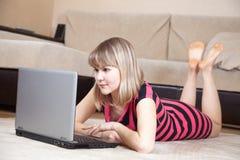 Muchacha que miente en suelo y que usa la computadora portátil Imagen de archivo