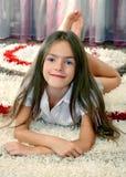 Muchacha que miente en una alfombra Imagenes de archivo