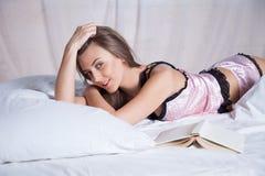 Muchacha que miente en una cama con el libro y la sonrisa Imagenes de archivo