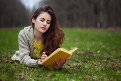 Muchacha que miente en una hierba y un libro de lectura Fotografía de archivo libre de regalías
