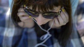 Muchacha que miente y que escucha la música en el teléfono fotografía de archivo libre de regalías