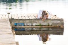 Muchacha que mira abajo de un embarcadero Foto de archivo