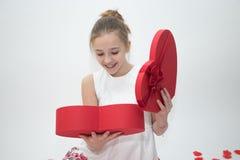 Muchacha que mira abajo en una caja que contiene un regalo que ella recibió para el día del ` s de la tarjeta del día de San Vale Imagenes de archivo