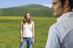 Muchacha que mira al novio mientras que se coloca en campo Fotos de archivo