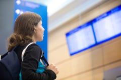 Muchacha que mira al tablero de la información del vuelo del aeropuerto Imagen de archivo libre de regalías