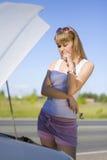 Muchacha que mira bajo el coche Imagen de archivo