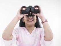 Muchacha que mira con el binocular Foto de archivo libre de regalías