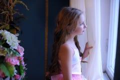 Muchacha que mira cuidadosamente fuera de la ventana Imagen de archivo libre de regalías