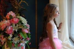 Muchacha que mira cuidadosamente fuera de la ventana Foto de archivo libre de regalías