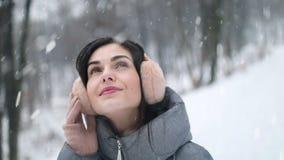 Muchacha que mira el cielo durante las nevadas en bosque almacen de metraje de vídeo
