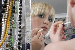 Muchacha que mira el espejo mientras que aplica el lápiz labial Fotografía de archivo