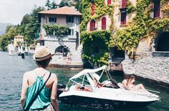 muchacha que mira el lago Como con los turistas en poco barco en Nesso, Lombardía, Italia imagenes de archivo