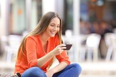 Muchacha que mira el medios contenido en un teléfono Foto de archivo libre de regalías