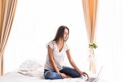muchacha que mira el monitor del ordenador portátil mientras que miente en cama en su sitio Imagenes de archivo