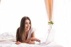muchacha que mira el monitor del ordenador portátil mientras que miente en cama en su sitio Fotografía de archivo