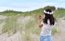 Muchacha que mira el pequeño espejo redondo Foto de archivo