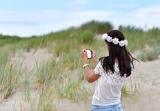 Muchacha que mira el pequeño espejo redondo Imagen de archivo