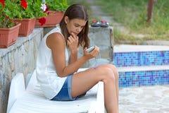 Muchacha que mira el teléfono Fotografía de archivo libre de regalías