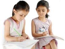 Muchacha que mira en el bool de su amigo mientras que estudia Fotos de archivo libres de regalías
