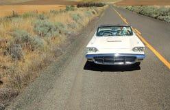 Muchacha que mira en el espejo de la vista posterior del convertible de Thunderbird Fotos de archivo