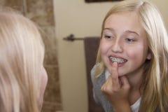 Muchacha que mira en el espejo, examinándola apoyos Foto de archivo libre de regalías