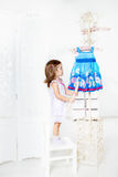 Muchacha que mira en el estante de la capa Fotos de archivo libres de regalías