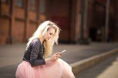 muchacha que mira en el teléfono Fotos de archivo