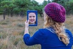 Muchacha que mira en espejo en naturaleza Foto de archivo