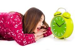 Muchacha que mira en la alarma mientras que su sonido Imagen de archivo