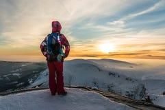 Muchacha que mira en la puesta del sol en el top de la montaña Imagen de archivo