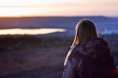 Muchacha que mira en un lago en la puesta del sol Imagen de archivo