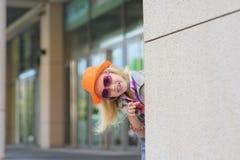 Muchacha que mira a escondidas a la vuelta de la esquina Fotos de archivo