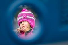 Muchacha que mira a escondidas a través del agujero fotos de archivo