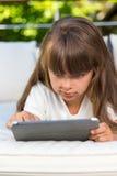Muchacha que mira fijamente la tableta Foto de archivo