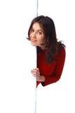 Muchacha que mira furtivamente sobre una cartelera Fotografía de archivo