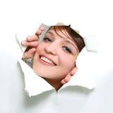 Muchacha que mira furtivamente a través del agujero en papel Fotografía de archivo