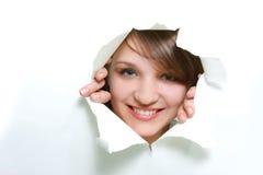 Muchacha que mira furtivamente a través del agujero en papel Fotos de archivo libres de regalías