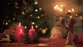 Muchacha que mira hacia fuera la tabla adornada para la celebración de la Navidad, atmósfera festiva metrajes