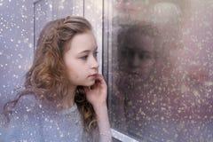 Muchacha que mira hacia fuera la ventana Fotos de archivo