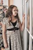 Muchacha que mira hacia fuera la ventana Imagen de archivo libre de regalías