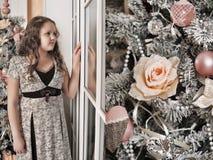 Muchacha que mira hacia fuera la ventana Imágenes de archivo libres de regalías