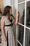 Muchacha que mira hacia fuera la ventana Foto de archivo libre de regalías
