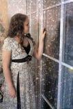 Muchacha que mira hacia fuera la ventana Foto de archivo
