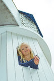Muchacha que mira hacia fuera la ventana de la torre Imagenes de archivo