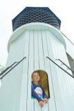 Muchacha que mira hacia fuera la ventana de la torre Foto de archivo