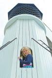 Muchacha que mira hacia fuera la ventana de la torre Fotografía de archivo libre de regalías