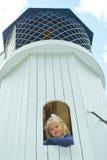 Muchacha que mira hacia fuera la ventana de la torre Fotos de archivo libres de regalías